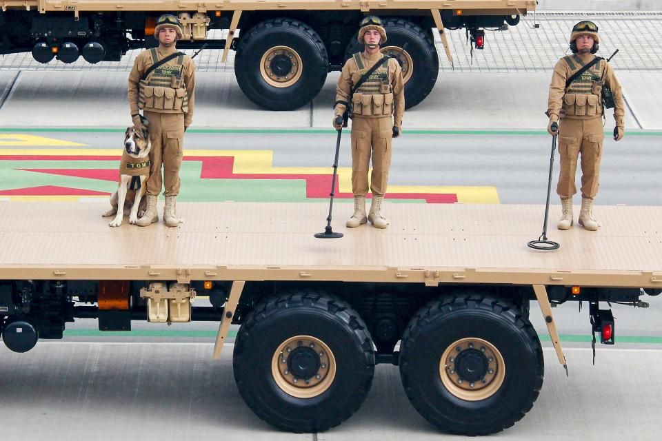 Turkmenistan's army demining soldiers, one of them with a shepherd dog Alabay, stand on a planform during a military parade celebrating the country's 30th independence anniversary in Ashgabat, Turkmenistan, Monday, Sept. 27, 2021. The pomp-filled parade took place in Ashgabat, the capital of the gas-rich former Soviet nation in Central Asia. Aside from troops and military equipment, the parade featured employees of state ministries and institutions demonstrating their achievements and Alabai dogs, which accompanied soldiers on military vehicles. (AP Photo/Alexander Vershinin)