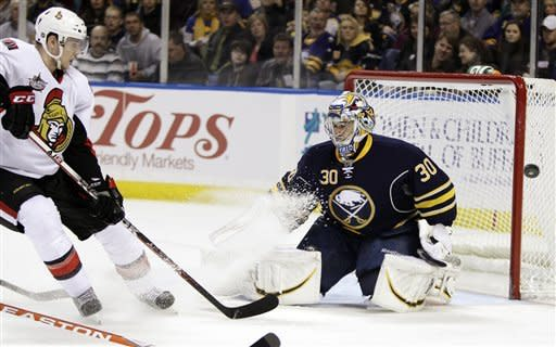 Buffalo Sabres goalie Ryan Miller (30) makes a save under pressure from Ottawa Senators' Colin Greening, left, during the second period of an NHL hockey game in Buffalo, N.Y., Tuesday, Dec. 13, 2011. (AP Photo/David Duprey)
