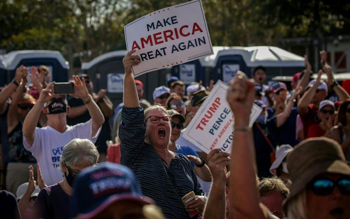 Thousands of unmasked supporters cheer as US Vice President Mike Pence speaks at a rally in The Villages, central Florida - AFP