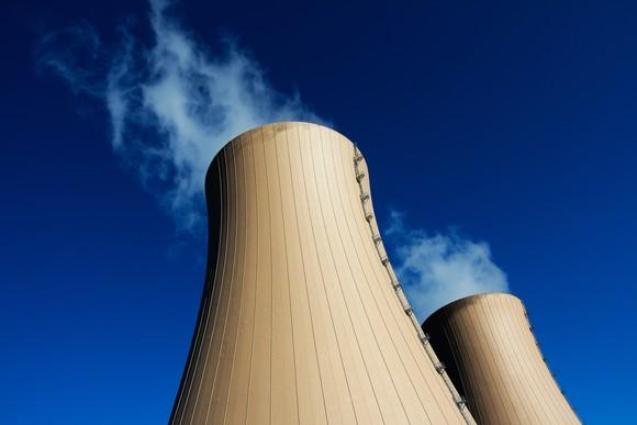 Cooling towers for a power plant against a blue sky.