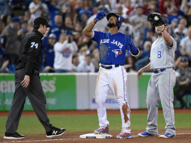 Toronto Blue Jays' Teoscar Hernandez celebrates his two-run triple as Kansas City Royals third baseman Mike Moustakas stands next to him during the seventh inning of a baseball game Wednesday, April 18, 2018, in Toronto. (Nathan Denette/The Canadian Press via AP)