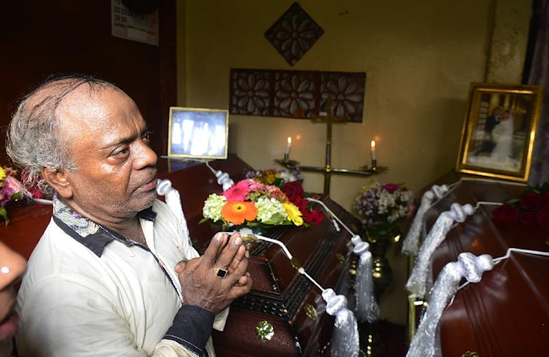 Baby Joseph Gomez -- the father of suicide blast victim Berlington Joseph Gomez -- mourns next to the coffins of his son, grandson and daughter-in-law at his home in Colombo (AFP Photo/LAKRUWAN WANNIARACHCHI)