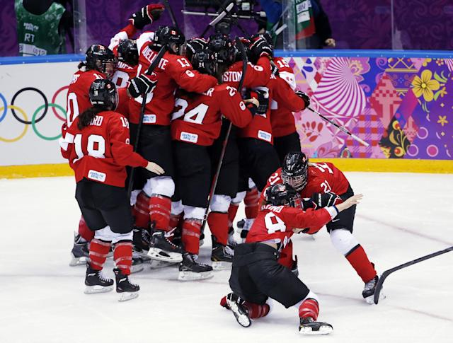 Canada celebrates after their 3-2 win in overtime against USA in the women's gold medal ice hockey game at the 2014 Winter Olympics, Thursday, Feb. 20, 2014, in Sochi, Russia. (AP Photo/Petr David Josek)
