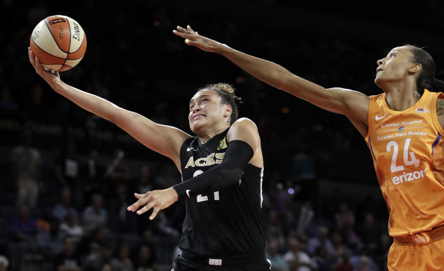 FILE - In this Aug. 1, 2018, file photo, Las Vegas Aces guard Kayla McBride shoots around Phoenix Mercury forward DeWanna Bonner during the second half of a WNBA basketball game in Las Vegas. McBride's eyes light up when talking about the Las Vegas offense. With the addition of 6-foot-8 Liz Cambage in the offseason to join 6-5 A'ja Wilson in the Aces' frontcourt, her life on the court as a shooter has gotten much easier. (AP Photo/John Locher, File)