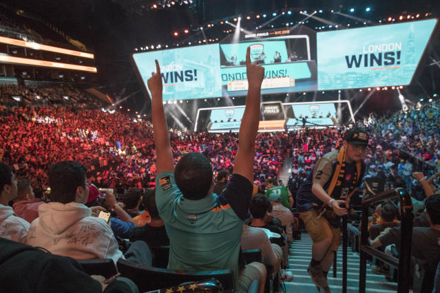 FILE - In this July 28, 2018, file photo, London Spitfire fan Rick Ybarra, of Plainfield, Ind., reacts after London won the second game against the Philadelphia Fusion during the Overwatch League Grand Finals competition at Barclays Center in New York. The Overwatch League took another step in its ambitious vision when franchises in Dallas and New York hosted season-opening matches last weekend. They were the first of 52 scheduled events on OWLs home-and-away calendar requiring teams to visit host arenas for all 20 teams spanning Europe, North America and Asia. (AP Photo/Mary Altaffer, File)