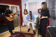 """Members of the folk group, The Staves, from left, sisters, Jessica, Camilla and Emily Staveley-Taylor rehearse in a north London recording studio, on Feb. 15, 2021. The Staves released their third album, """"Good Woman,"""" last month. (Photo by Joel C Ryan/Invision/AP)"""