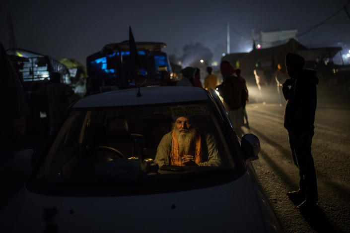 """Farmer Bhupinder Singh, 50, sits inside his car parked on a highway as a sign of protest against new farm laws, at the Delhi-Haryana state border, India, Wednesday, Dec. 2, 2020. The convoy of trucks, trailers and tractors stretches for at least three kilometers (1.8 miles). It's a siege of sorts and the mood among the protesting farmers is boisterous. Their rallying call is """"Inquilab Zindabad"""" (""""Long live the revolution""""). (AP Photo/Altaf Qadri)"""