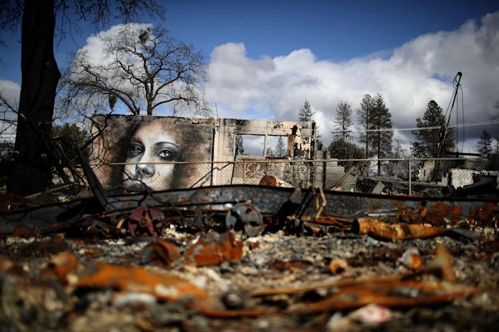 A mural by artist Shane Grammer is visible on the wall of a building destroyed by the 2018 wildfire that destroyed the town of Paradise, California. Climate change is leading to more intense and more frequent wildfires. (Photo: Justin Sullivan via Getty Images)