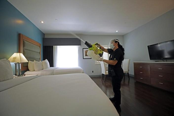"A worker at a hotel in Studio City uses a handheld machine to spray a disinfectant fog made of ethanol and hydrogen peroxide. <span class=""copyright"">(Myung J. Chun/Los Angeles Times)</span>"