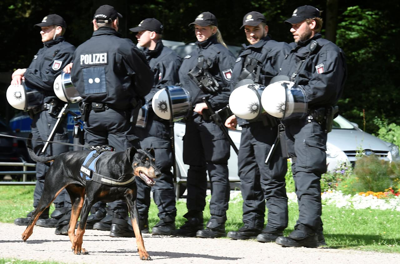 A dog passes a row of police men during a G20 demonstration against the ban of Hamburg's authorities of a G20 protestors camp in the Stadtpark park in Hamburg, Germany June 26, 2017. REUTERS/Fabian Bimmer