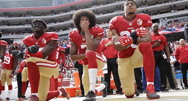From left, 49ers outside linebacker Eli Harold, quarterback Colin Kaepernick, and safety Eric Reid on Oct. 2, 2016, during the national anthem. (AP)