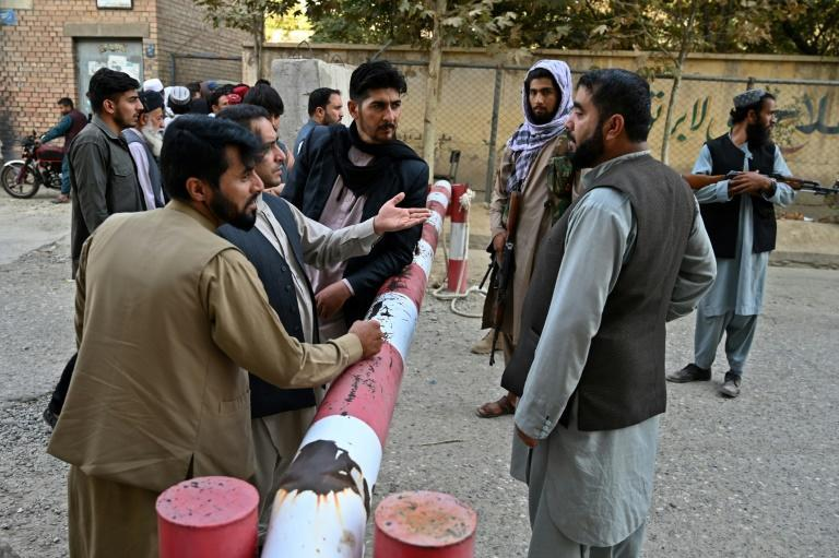Hundreds of people flocked to the department to apply for travel documents in a test of the new Afghan government's commitment to allow eligible people to leave (AFP/WAKIL KOHSAR)