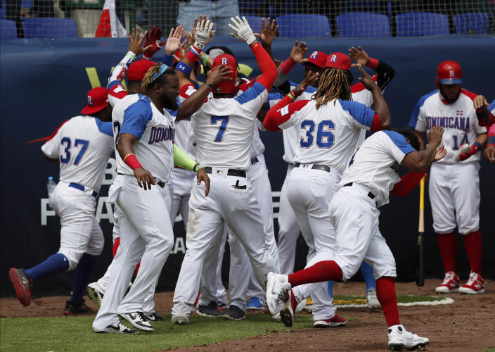 Dominican Republic catcher Charlie Valerio (7) is congratulated by his teammates after he scored a run against Venezuela during a final Olympic baseball qualifier game, in Puebla, Mexico, Saturday, June 26, 2021. (AP Photo/Fernando Llano)