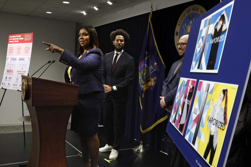 New York State Attorney General Letitia James speaks during a news conference at her office in New York, Tuesday, Nov. 19, 2019. New York has joined the ranks of states suing the nation's biggest e-cigarette maker, San Francisco based JUUL Labs. At background left and right are Andre Richardson, campaign manager of Flavors Hook Kids, and East Hampton High School Principal Adam Fine. (AP Photo/Richard Drew)