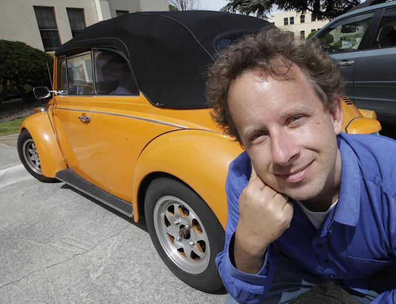 In this April 12, 2012 photo, Kaggle's president and chief scientist Jeremy Howard poses with an orange Volkswagen in Mountain View, Calif. The founders of San Francisco startup Kaggle believe the problems data scientists solve are so important that they should be paid like professional athletes. By turning data science into a crowd-sourced contest, they hope they have created a way to make that happen. Kaggle hopes top contenders will participate in a sport tailor-made for the 21st century: Competitive number-crunching. As part of a study Howard found orange used cars are more likely to be a lemon. (AP Photo/Paul Sakuma)