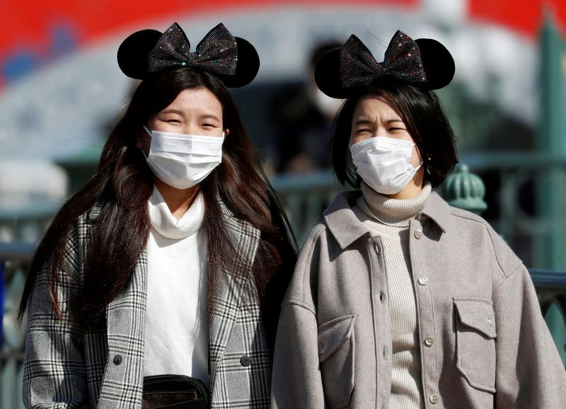 Visitors wearing protective face masks and Mickey Mouse costumes, following an outbreak of the coronavirus, are seen outside Tokyo Disneyland in Urayasu
