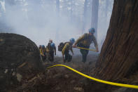 Members of a hotshot crew hike up the mountain while battling the Caldor Fire in South Lake Tahoe, Calif., Friday, Sept. 3, 2021. Fire crews took advantage of decreasing winds to battle a California wildfire near popular Lake Tahoe and were even able to allow some people back to their homes but dry weather and a weekend warming trend meant the battle was far from over. (AP Photo/Jae C. Hong)