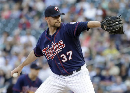 Minnesota Twins' Mike Pelfrey winds up on a pitch against the Seattle Mariners in the first inning of a baseball game, Friday, May 31, 2013, in Minneapolis. (AP Photo/Jim Mone)