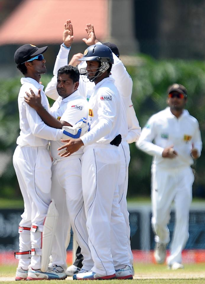 Sri Lankan cricketer Rangan Herath (2L) celebrates with his teammates the dismissal of Bangladeshi cricketer Mohammad Mahmudullah during the third day of the opening Test match between Sri Lanka and Bangladesh at the Galle International Cricket Stadium in Galle on March 10, 2013.   AFP PHOTO/ LAKRUWAN WANNIARACHCHI        (Photo credit should read LAKRUWAN WANNIARACHCHI/AFP/Getty Images)