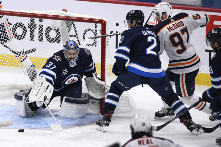 Winnipeg Jets goaltender Connor Hellebuyck (37) clears the puck as Dylan DeMelo (2) defends against Edmonton Oilers' Connor McDavid (97) during the first period of an NHL hockey game Tuesday, Jan. 26, 2021, in Winnipeg, Manitoba. (Fred Greenslade/The Canadian Press via AP)