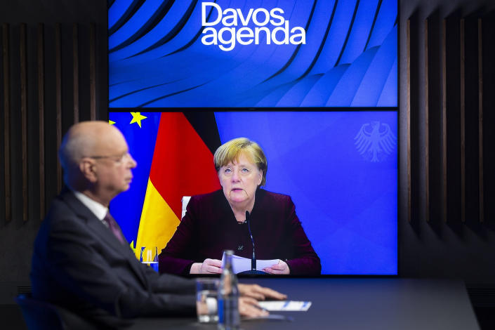 German Klaus Schwab, left, Founder and Executive Chairman of the World Economic Forum, WEF, listens to German Chancellor Angela Merkel, displayed on a video screen, during a conference at the Davos Agenda in Cologny near Geneva, Switzerland, Tuesday, Jan. 26, 2021. The Davos Agenda from Jan. 25 to Jan. 29, 2021 is an online edition due to the coronavirus disease (COVID-19) outbreak. (Salvatore Di Nolfi/Keystone via AP)