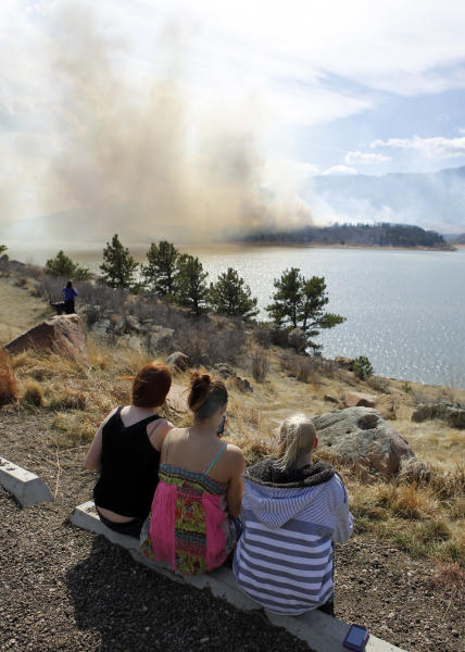 RETRANSMISSION TO CORRECT LOCATION - From left, Kelly Burrell, Myam Siegler and Callie Mowers watch a wildfire as it burns out of control at Horsetooth Reservoir west of Fort Collins, Colo., on Friday, March 15, 2013. The 40-acre wildfire burning in gusty winds and warm weather was threatening homes west of Fort Collins on Friday and prompted about 50 people to leave the area. (AP Photo/Ed Andrieski)
