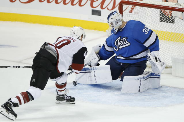 Winnipeg Jets goaltender Laurent Brossoit (30) saves a breakaway-attempt by Arizona Coyotes' Michael Grabner (40) during first-period NHL hockey game action in Winnipeg, Manitoba, Saturday, Oct. 20, 2018. (John Woods/The Canadian Press via AP)