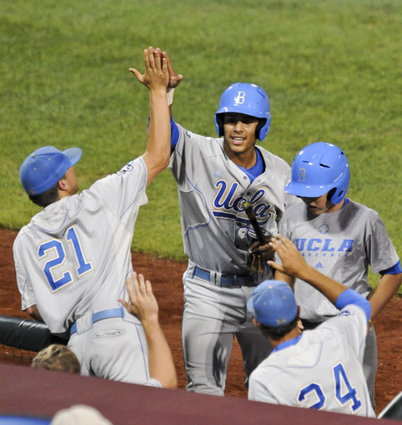 UCLA's Kevin Williams, center is greeted at the dugout by teammate Nick Vander Tuig (21) after scoring against Florida State on a single by Cody Keefer, in the sixth inning of an NCAA College World Series elimination baseball game in Omaha, Neb., Tuesday, June 19, 2012. (AP Photo/Dave Weaver)