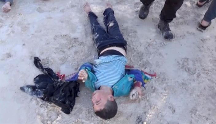 <p>A still image taken from a video posted to a social media website on April 4, 2017, shows a boy lying on the ground said to be in the town of Khan Sheikhoun, after what rescue workers described as a suspected gas attack in rebel-held Idlib, Syria. (Social Media Website via Reuters TV) </p>