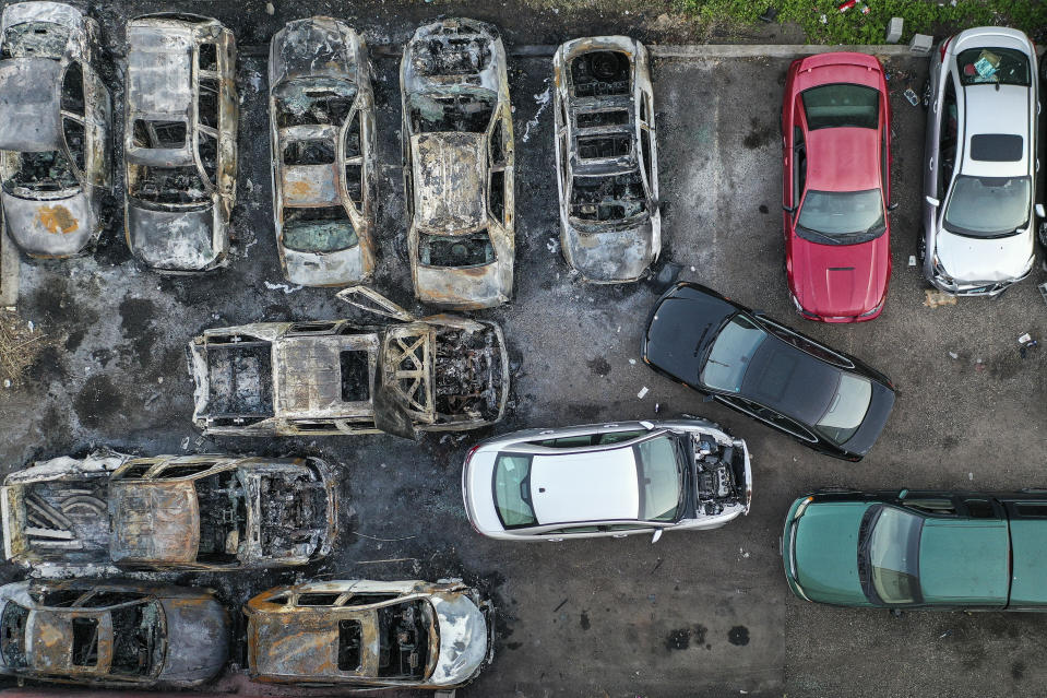 Burnt vehicles remain in a parking lot along East Lake Street after they were destroyed in a protest two days prior, Tuesday, June 2, 2020, in Minneapolis. Protests continued following the death of George Floyd, who died after being restrained by Minneapolis police officers on May 25. (AP Photo/John Minchillo)