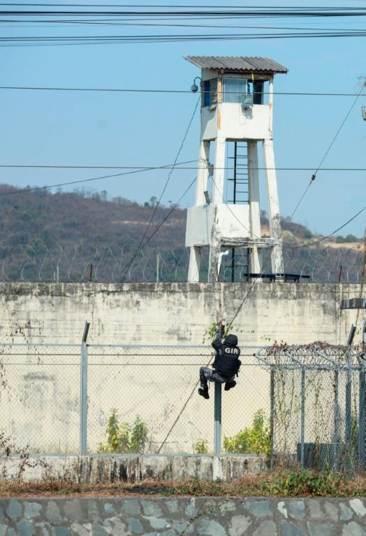 A riot police officer climbs the security fence as deadly violence broke out at the Guayaquil prison on September 28, 2021 in Ecuador (AFP/Fernando Mendez)
