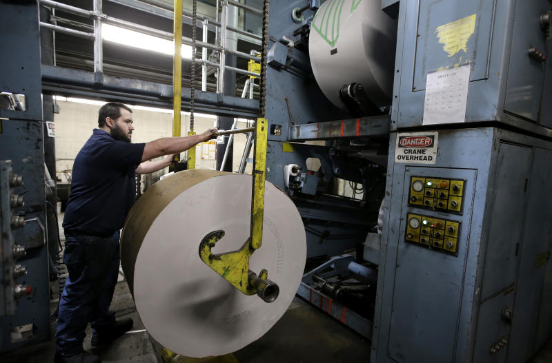 In this Thursday, April 11, 2019 photo pressman Adam Doucette, of Pittsfield, Mass., prepares a roll of paper for printing presses at The Berkshire Eagle newspaper, in Pittsfield. The paper now features a new 12-page lifestyle section for Sunday editions, a reconstituted editorial board, a new monthly magazine, and the newspaper print edition is wider. That level of expansion is stunning in an era where U.S. newspaper newsroom employment has shrunk by nearly half over the past 15 years. (AP Photo/Steven Senne)