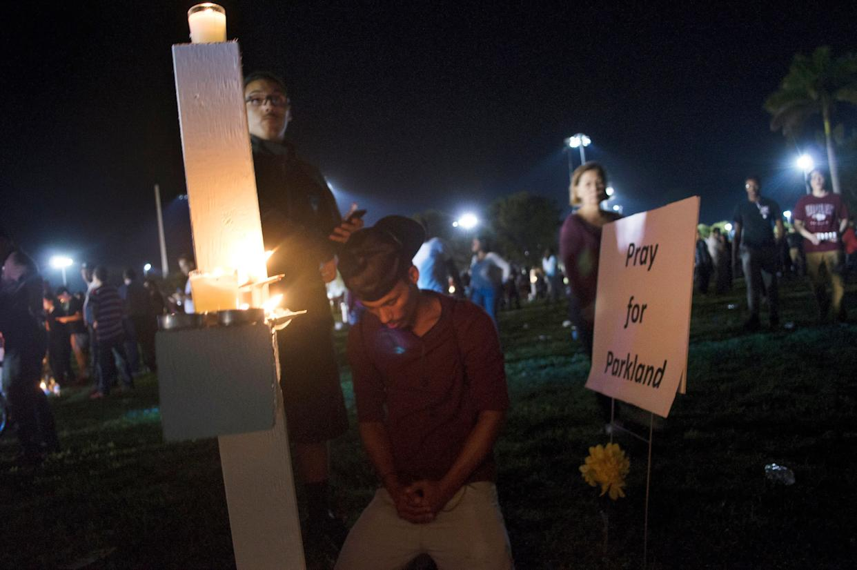 Jay Eaton, 19, prays at a vigil Thursday night, one day after a school shooting left 17 people dead.