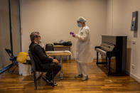 A health professional conducts a coronavirus test on an employee at the Teatro Real in Madrid, Spain, on Wednesday, Nov. 18, 2020. The theater is one of the few major opera houses that have reopened during the coronavirus pandemic, although to smaller audiences. (AP Photo/Bernat Armangue)
