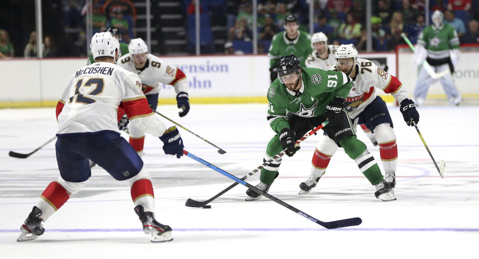 Dallas Stars' Tyler Seguin tries to move the puck against Florida Panthers defenders Ian McCoshen (12), Dominic Toninato (9) and Anthony Greco (76) during the third period of a preseason NHL hockey game in Tulsa, Okla., Saturday, Sept. 21, 2019. (AP Photo/Dave Crenshaw)