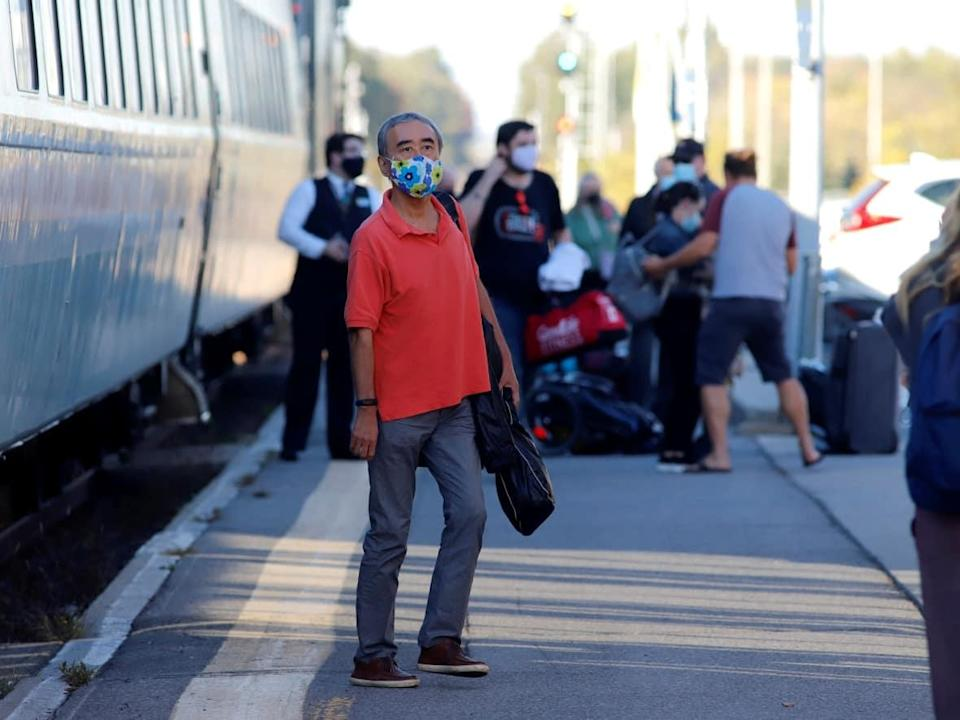 Via Rail passengers disembark a train in Ottawa earlier this week as Prime Minister Justin Trudeau announced passengers will require COVID-19 shots for air, ship and interprovincial rail travel. (Patrick Doyle/Reuters - image credit)