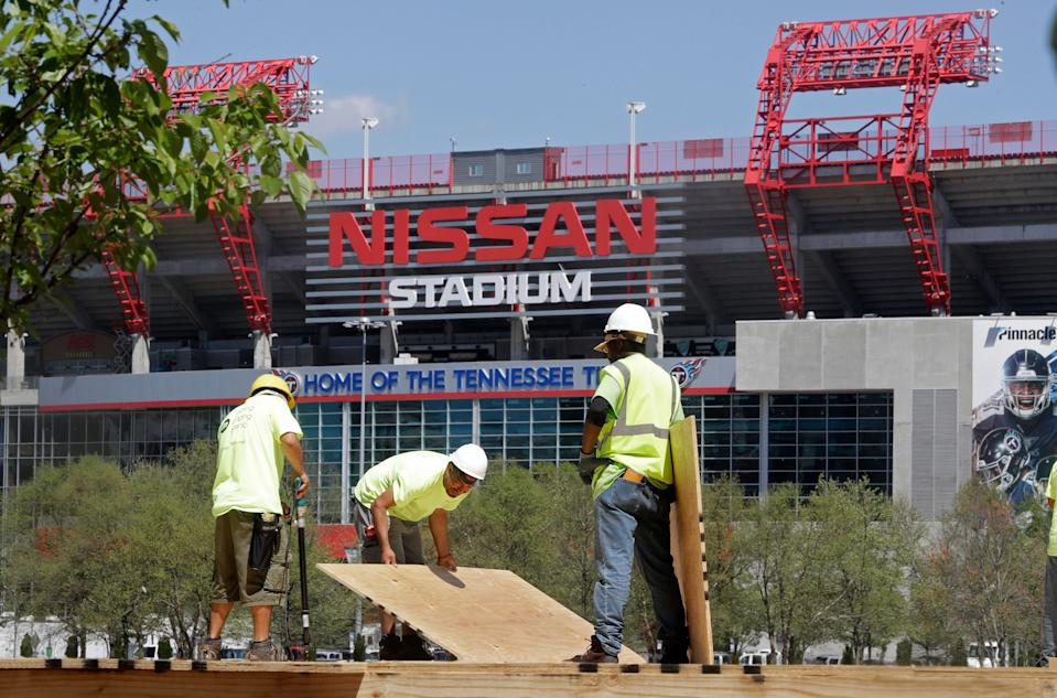 Workers build the foundation for a structure for the NFL Draft Tuesday, April 9, 2019, in Nashville, Tenn. Across the river is Nissan Stadium, home of the Tennessee Titans. The NFL Draft is scheduled to be held outdoors in downtown Nashville April 25-27. (AP Photo/Mark Humphrey)