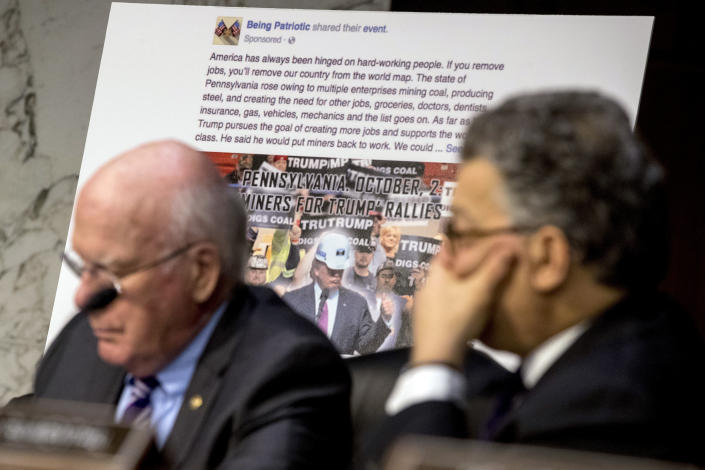 A poster depicting an example of a misleading Internet posting is visible as Sen. Patrick Leahy, D-Vt., left, Sen. Al Franken, D-Minn., listen to testimony. (AP Photo/Andrew Harnik)