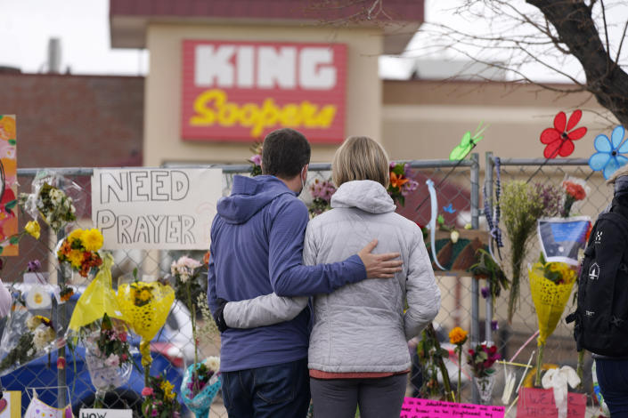 FILE - In this March 26, 2021, file photo, mourners walk the temporary fence line outside the parking lot of a King Soopers grocery store, the site of a mass shooting in Boulder, Colo. Colorado prosecutors have filed over 40 more felony charges against the man charged with killing 10 people at the Boulder supermarket last month — including allegations he used a large capacity magazine that had been banned by state lawmakers in 2013 in response to mass shootings. (AP Photo/David Zalubowski, File)