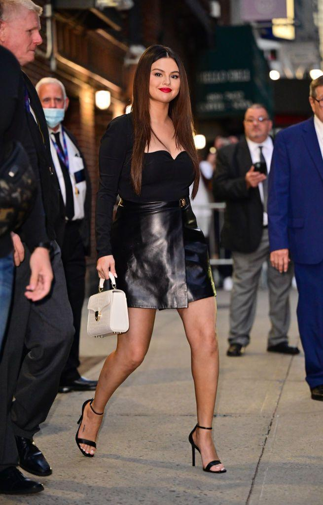 """<p>Visiting the Late Show with Stephen Colbert to discuss her new TV show Only Murders In The Building, Gomez exited wearing the perfect 'out-out' look: A black top with a sweetheart neckline, wrap leather-style skirt and carrying a white Aspinal Mayfair midi-bag.</p><p><a class=""""link rapid-noclick-resp"""" href=""""https://go.redirectingat.com?id=127X1599956&url=https%3A%2F%2Fwww.aspinaloflondon.com%2Fproducts%2Fmidi-mayfair-bag-in-ivory-patent-croc&sref=https%3A%2F%2Fwww.elle.com%2Fuk%2Ffashion%2Fcelebrity-style%2Farticles%2Fg10775%2Fselena-gomez-style-file-red-carpet-dresses-street-style%2F"""" rel=""""nofollow noopener"""" target=""""_blank"""" data-ylk=""""slk:SHOP NOW"""">SHOP NOW</a> Aspinal Midi Mayfair bag in Ivory, £595</p>"""