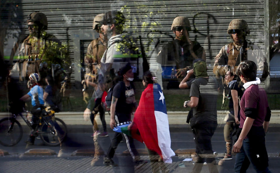 Soldiers are reflected in the glass of a bus stop as demonstrators walk past, amid ongoing demonstrations triggered by an increase in subway fares in Santiago, Chile, Monday, Oct. 21, 2019. (Photo: Luis Hidalgo/AP)