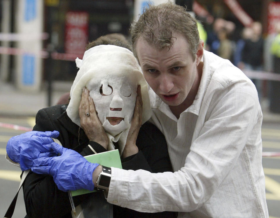 FILE - In this Thursday July 7, 2005 file photo Paul Dadge, right, helps injured tube passenger Davinia Turrell away from Edgware Road tube station in London following an explosion. In the 20 years since the Sept. 11, 2001 terrorist attacks in the United States, a mixture of homegrown extremists, geography and weaknesses in counterterrorism strategies have combined to turn Europe into a prime target for jihadists bent on hurting the West. (AP Photo/Jane Mingay, File)