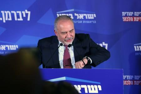 Avigdor Lieberman, leader of Yisrael Beitenu party looks at his watch as he speaks following the announcement of exit polls in Israel's parliamentary election at his party headquarters in Jerusalem