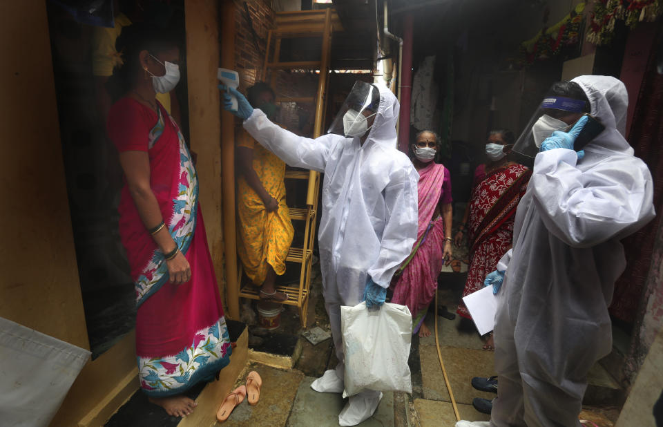 A health worker checks the body temperature of a resident, as others await their turn during a free medical checkup in a slum in Mumbai, India, Sunday, June 28, 2020. India is the fourth hardest-hit country by the COVID-19 pandemic in the world after the U.S., Russia and Brazil. (AP Photo/Rafiq Maqbool)