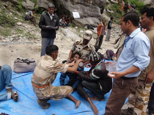 In this handout photograph received from the Indo Tibetan Border Police (ITBP) on June 25, 2013, members of the ITBP revive a stranded person at Pandukeshwar in northern Uttarakhand state. Indian officials stepped up efforts on June 25 to prevent an outbreak of disease in the northern Himalayan region devastated by landslides and flash floods, as rains hampered the rescue of thousands still stranded. AFP PHOTO/ITBP