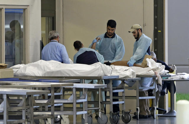 <p>Medical personnel examine a body at the Orlando Medical Examiner's Office , Sunday, June 12, 2016, in Orlando, Fla. A gunman opened fire inside a crowded gay nightclub early Sunday, before dying in a gunfight with SWAT officers, police said. (AP Photo/Alan Diaz) </p>