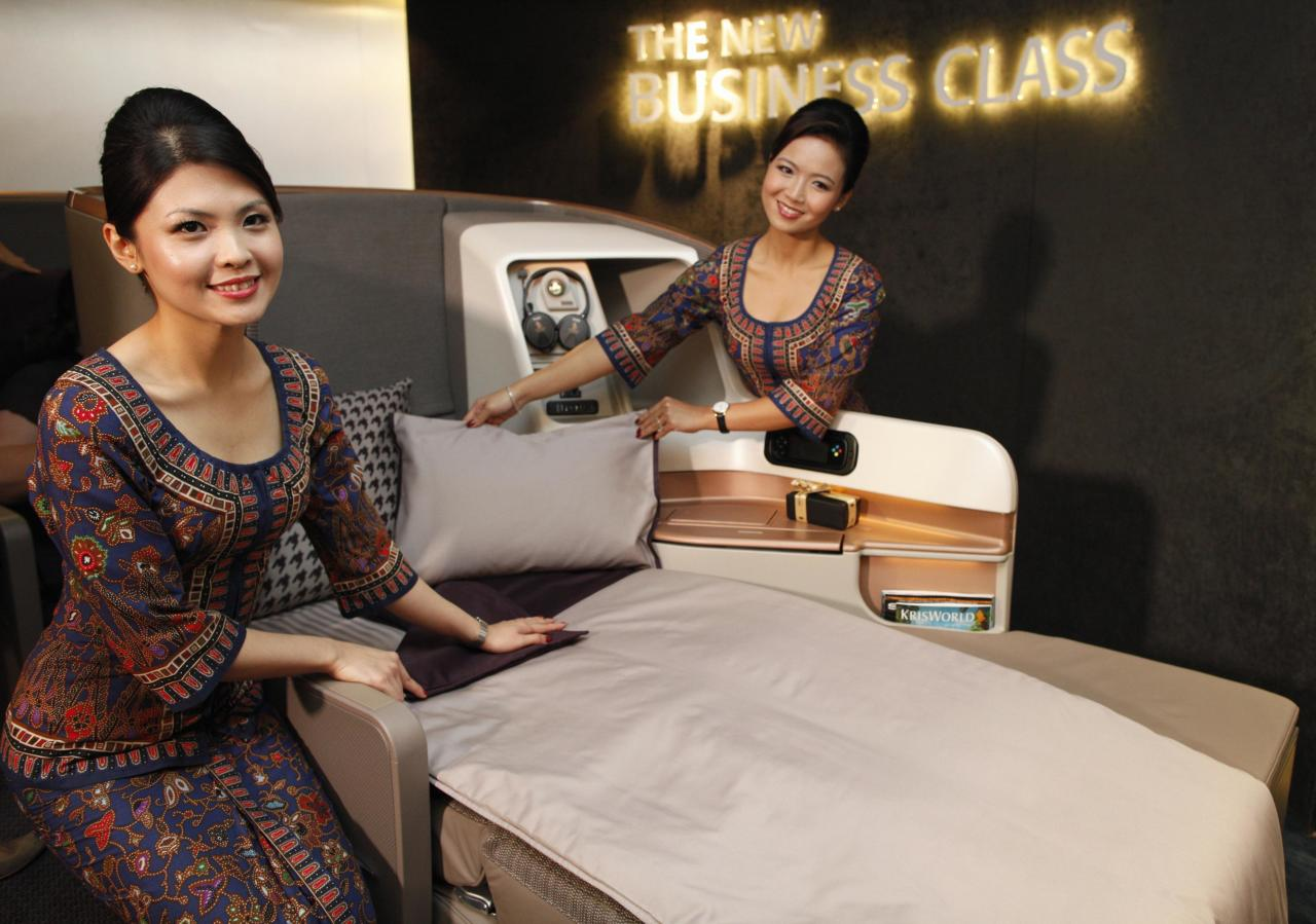 Singapore Airlines Ltd stewardesses pose next to a business class seat during the launch of their new generation of cabin products at Changi Airport in Singapore July 9, 2013. The new seats and in-flight entertainment system, an investment of nearly $150 million by the company, will be rolled out from September, starting with flights between Singapore and London on eight Boeing 777-300ER aircrafts. REUTERS/Edgar Su (SINGAPORE - Tags: TRANSPORT BUSINESS)