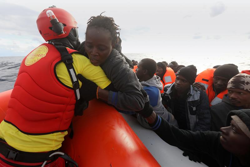 A lifeguard pulls a migrant woman to a rescue craft from an overcrowded raft in the central Mediterranean Sea, some 36 nautical miles off the Libyan coast, Jan. 2, 2017. (Yannis Behrakis / Reuters)