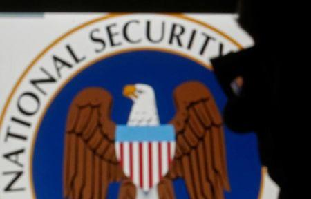 A man is silhouetted near logo of the U.S. National Security Agency (NSA) in this photo illustration taken in Sarajevo