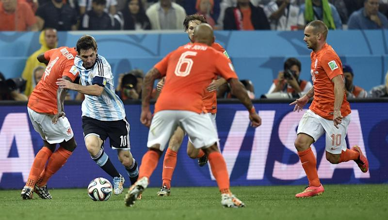 Argentina's Lionel Messi, second left, takes on the Dutch defence during the World Cup semifinal soccer match between the Netherlands and Argentina at the Itaquerao Stadium in Sao Paulo Brazil, Wednesday, July 9, 2014. (AP Photo/Martin Meissner)